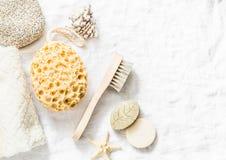 Аксессуары ливня - смотрите на щетку, губку, камень пемзы, полотенце, мыло на светлой предпосылке, взгляд сверху Очищать здоровья стоковое фото rf