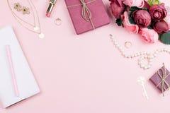 Аксессуары моды женщины, цветки, косметики и ювелирные изделия на розовой предпосылке, copyspace Стоковое Изображение