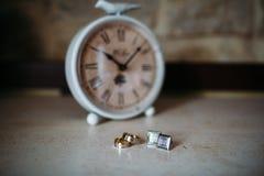 Аксессуары свадьбы Кольца золота и запонки для манжет на белых текстурированных таблице и часах на предпосылке Стоковые Изображения