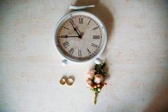 Аксессуары свадьбы Boutonniere, золотые кольца, красивый букет цветков на белой текстурированной таблице Концепция невесты Стоковая Фотография RF