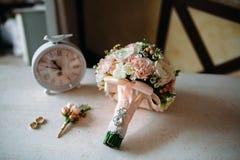 Аксессуары свадьбы Boutonniere, золотые кольца, красивый букет цветков на белой текстурированной таблице Концепция невесты Стоковые Фотографии RF