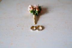 Аксессуары свадьбы Boutonniere, золотые кольца, красивый букет цветков на белой текстурированной таблице Концепция невесты Стоковая Фотография