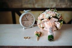 Аксессуары свадьбы Boutonniere, золотые кольца, красивый букет цветков на белой текстурированной таблице Концепция невесты Стоковое Фото