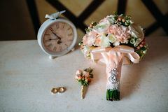 Аксессуары свадьбы Boutonniere, золотые кольца, красивый букет цветков на белой текстурированной таблице Концепция невесты Стоковое Изображение RF