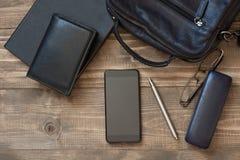 Аксессуары сумки плеча компьтер-книжки, черни, тетради, ручки и людей для дела на борту Взгляд сверху Плоское положение Стоковые Изображения