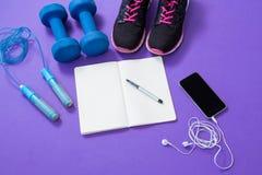 Аксессуары фитнеса с раскрытыми книгой и мобильным телефоном Стоковые Фото