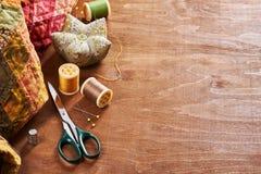 Аксессуары для заплатки на лоскутном одеяле на деревянной предпосылке Стоковое фото RF
