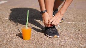 Активная атлетическая женщина связывая шнурки ботинка и выпивая свежий апельсиновый сок перед бежать в парке 4K bangkok Таиланд сток-видео