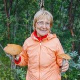 Активная более старая женщина - подборщик гриба, вдыхает запах белых грибов нашел он Стоковое Изображение RF