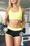 Активная женщина в атлетических зеленых одеждах включена с гантелью в спортзале Прочность воли красивейшее тело Стоковая Фотография RF