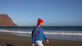 Активная женщина hiker идет на пляж Кавказская молодая женщина с рюкзаком на Тенерифе, Канарских островах, Испании сток-видео