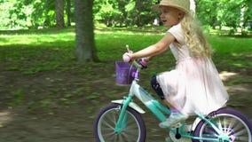 Активная красивая белокурая езда девушки быстро ее велосипед в переулке дерева Карданный подвес следовать видеоматериал