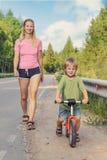 Активная мама идя с ребенк с велосипедом стоковые изображения