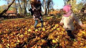 Активная мама с детьми имеет потеху между листьями осени в парке сток-видео