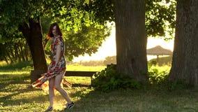Активная молодая женщина в красочном повороте платья на выравнивать свет захода солнца ( акции видеоматериалы