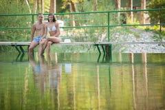 Активная пара отдыхает на речном береге на горячий летний день Стоковые Изображения