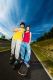Активное молодые люди - rollerblading, skateboarding Стоковые Изображения
