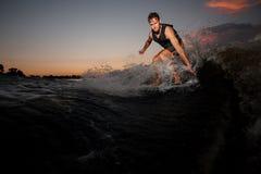 Активное wakesurfer скача на ехать вниз с реки развевает a Стоковые Изображения