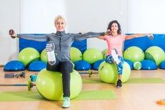 Активные женщины сидя на шариках тренировки поднимая ноги и делая повышение гантели боковое 2 зрелых женщины разрабатывая внутри Стоковые Фото