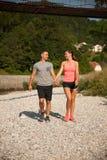 Активные молодые пары на прогулке на речном береге на горячем afterno лета Стоковые Изображения
