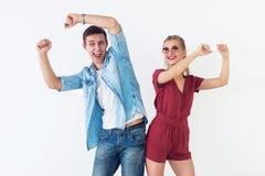 Активные молодые пары друзей имея полезного время работы, поднимающ руки вверх, танцевать, смеясь над совместно на белой предпосы стоковые фото