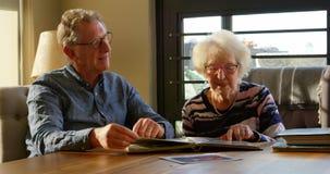 Активные старшие пары смотря фотоальбом 4k видеоматериал