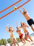 Активные люди играя шарик на пляже Стоковые Изображения