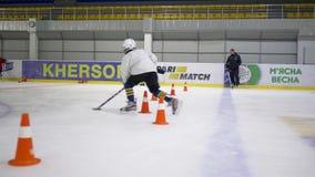 Активный игрок ребенк с управлением хоккейной клюшки шайба с препонами между конусами дороги на льде внутри катка сток-видео