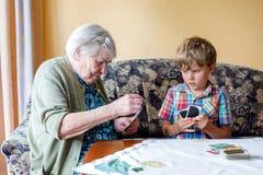Активный маленький мальчик ребенк preschool и грандиозная бабушка играя карточную игру совместно дома стоковое изображение rf