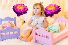 Активный маленький ребенок дошкольного возраста, милая маленькая девочка с белокурым вьющиеся волосы, игры с ее куклами, кладет и Стоковые Фото