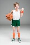Активный мальчик в sportswear с шариком баскетбола на сером цвете Стоковое Изображение RF