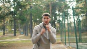 Активный молодой человек в фуфайке делает спорт в боксе парка самостоятельно в оружиях рекреационной области двигая на летний ден сток-видео