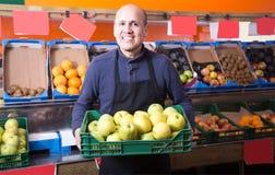 Активный мужской поставщик продавая яблока в гастрономе Стоковые Изображения