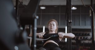 Активный образ жизни и спорт, молодая счастливая красноволосая женщина, которая тренируется на гребной машине в тренажерном зале  видеоматериал