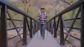 Активный пеший туризм женщины идет через мост реки в парке США Сиона Стоковое Изображение