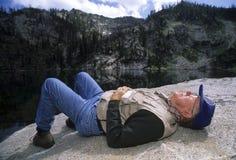 Активный старший человек napping на утесе Стоковое фото RF