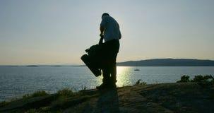 Активный человек с рюкзаком располагаясь лагерем на moutain морем на заходе солнца