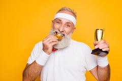 Активный эмоциональный холодный grandpa держа вознаграждение, есть металл s стоковая фотография