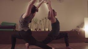 2 активных женщины симметрично делая тренировки йоги сток-видео