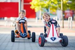 2 активных мальчика маленького ребенка управляя гоночными машинами педали Стоковые Фото