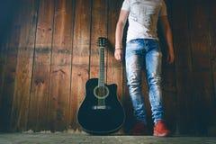 Акустическая гитара на деревянной текстуре с космосом экземпляра для текста и гитариста Концепция музыки и отдыха Гитара против д Стоковые Изображения