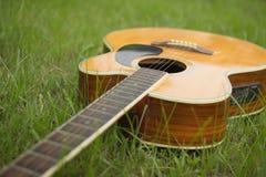 Акустическая гитара на траве с винтажным и мягким фокусом Стоковое Изображение