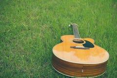 Акустическая гитара на траве с винтажным и мягким фокусом Стоковая Фотография