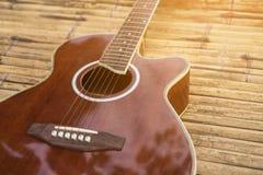 Акустическая гитара помещенная на деревянном столе Стоковое Изображение RF