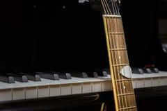 Акустическая гитара против ключей рояля Стоковое Изображение