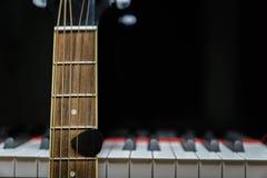 Акустическая гитара против ключей рояля Стоковая Фотография