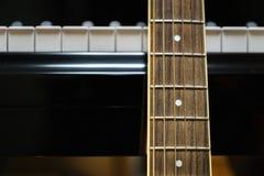 Акустическая гитара против ключей рояля Стоковая Фотография RF