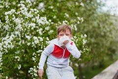Аллергическая реакция к цвести, мальчик с салфеткой в его руках стоковые фото