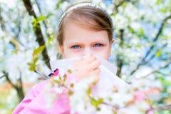 аллергически Маленькая девочка дует ее нос около дерева весны в blo стоковое изображение