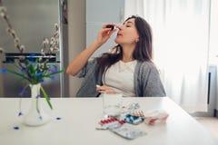 Аллергия весны Женщина используя носовые падения против сезонной аллергии и принимающ таблетки на кухне микстура гигиены медицинс стоковые изображения rf